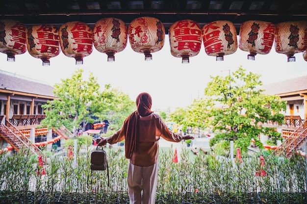 Punto di vista posteriore del turista musulmano della donna che sta sulla bella atmosfera cinese della casa, donna asiatica in vacanza. concetto di viaggio. tema cinese.