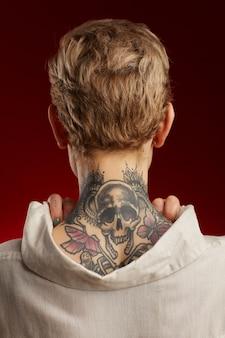 Vista posteriore del tatuaggio del collo con cranio e farfalle sulla giovane donna dai capelli corti in posa contro il muro rosso