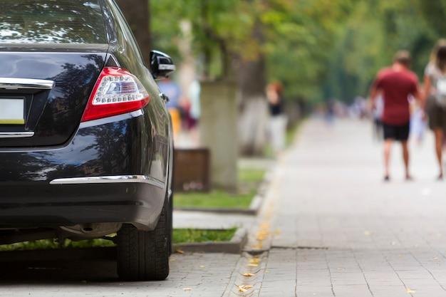 Parte di vista posteriore dell'auto lucida di lusso nera parcheggiata sul marciapiede della zona pedonale della città su sfondo di sagome sfocate di persone che camminano lungo il vicolo verde estivo soleggiato. concetto di stile di vita moderno.