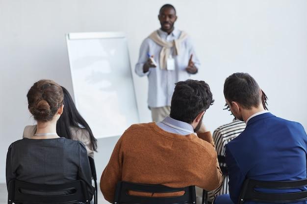 Vista posteriore delle persone sedute tra il pubblico alla conferenza di lavoro o al seminario educativo e ascoltando l'allenatore, copiando lo spazio