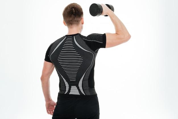 La foto posteriore di forte sportivo fa esercizi sportivi