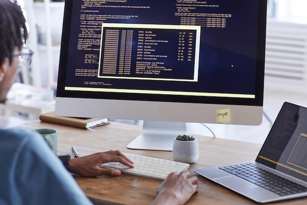 Ritratto di vista posteriore dell'uomo afro-americano che scrive codice sullo schermo del computer mentre si lavora alla scrivania in studio di sviluppo it, copia dello spazio