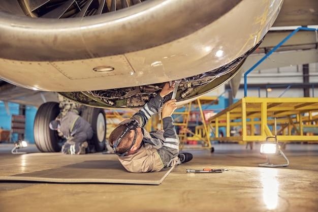 Vista posteriore ritratto di ingegnere aeronautico sdraiato sulla schiena sotto il motore aperto mentre fissa e controlla il sistema di aerei passeggeri nell'hangar