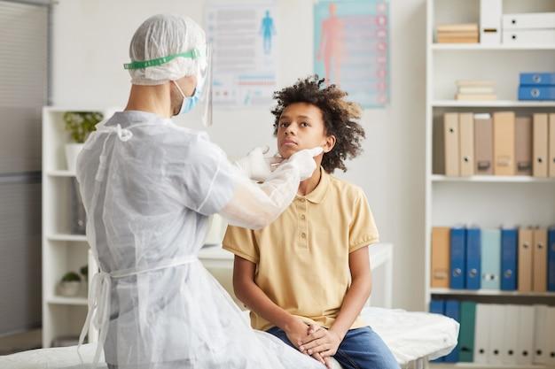 Vista posteriore ritratto del medico che esamina la gola del ragazzo afroamericano durante la consultazione in clinica, copia spazio