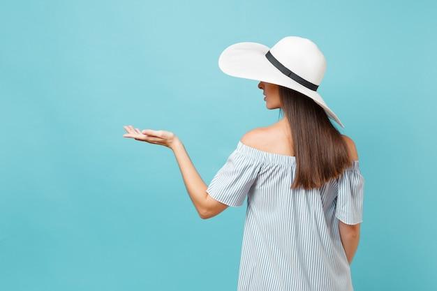 Vista posteriore ritratto di giovane donna di moda elegante in cappello da sole a tesa larga estate bianco, vestito messo le mani sulla testa, guardando da parte sullo spazio copia isolato su sfondo blu pastello. concetto di stile di vita.