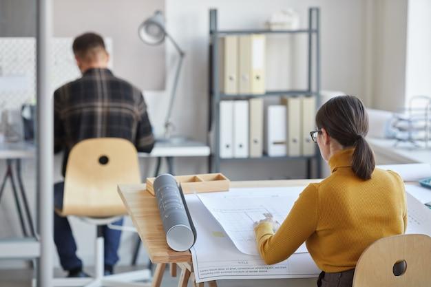 Vista posteriore ritratto di donna architetto cianografie di disegno mentre è seduto alla scrivania e lavora in ufficio,