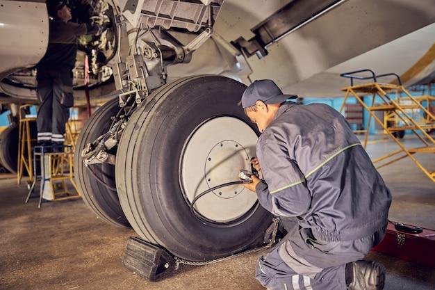 Ritratto di vista posteriore del tecnico di terra che lavora all'aeroporto che ripara gli aerei e controlla il carrello di atterraggio