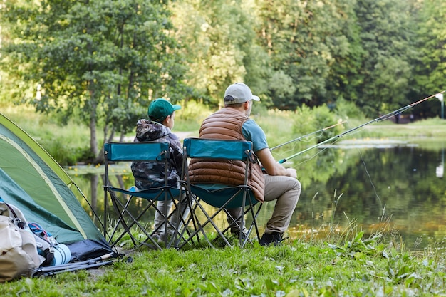 Vista posteriore ritratto di amorevole padre e figlio che pescano in riva al lago insieme durante il viaggio in campeggio in natura, copia spazio