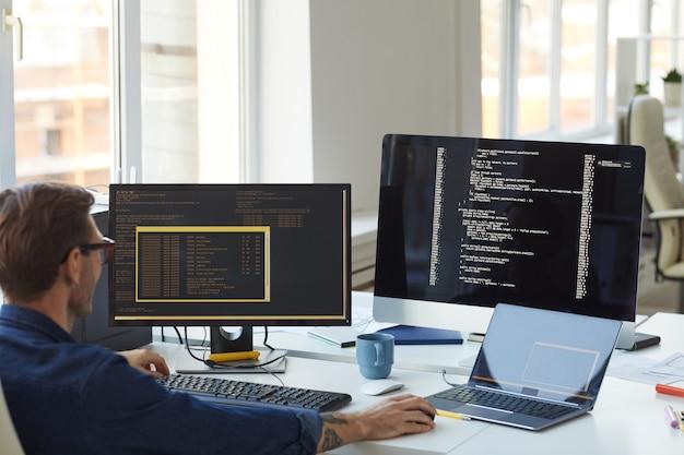 Vista posteriore ritratto del programmatore maschio che scrive codice sullo schermo del computer nell'ufficio degli sviluppatori it, copia spazio