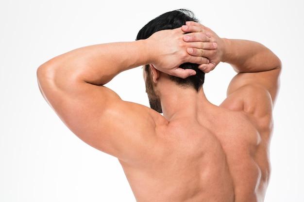 Ritratto di vista posteriore di un uomo con corpo muscoloso in piedi isolato su un muro bianco