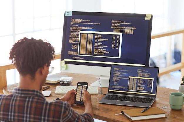 Ritratto di vista posteriore dell'uomo afroamericano moderno che tiene smartphone con codice sullo schermo mentre si lavora alla scrivania in ufficio, concetto di sviluppatore it, spazio di copia