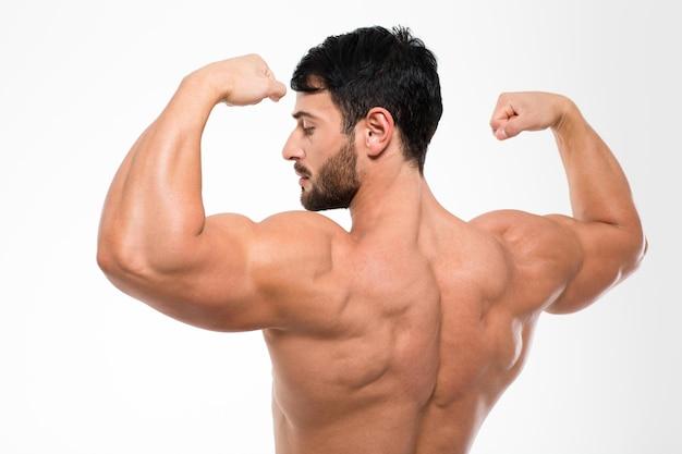 Ritratto di vista posteriore di un uomo muscoloso in piedi isolato su un muro bianco