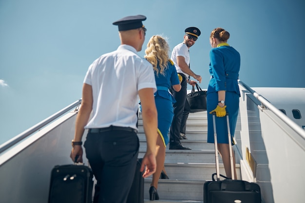 Vista posteriore ritratto di due assistenti di volo e due pilota senior con bagagli che salgono sulla scala dell'aereo di fronte all'aereo civile