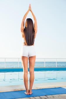 Ritratto di vista posteriore di una donna in piedi in posa yoga all'aperto