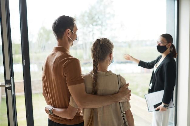 Vista posteriore ritratto di giovane coppia che ascolta l'agente immobiliare durante il tour dell'appartamento, copia spazio