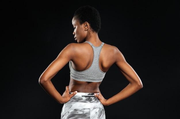 Vista posteriore ritratto di una giovane donna che allunga le mani isolate su un muro bianco