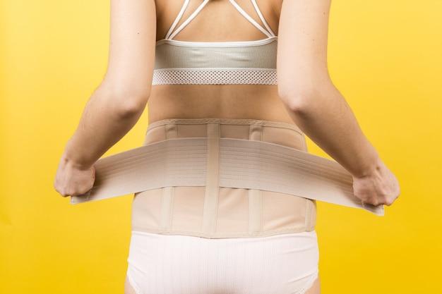 Vista posteriore della donna incinta in biancheria intima che veste corsetto ortopedico per far andare via il mal di schiena a sfondo giallo con spazio di copia. primo piano del concetto di cintura di supporto addominale ortopedico.