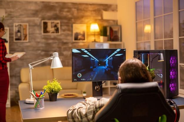 Vista posteriore di un videogiocatore professionista che gioca su un potente pc a tarda notte nel soggiorno.