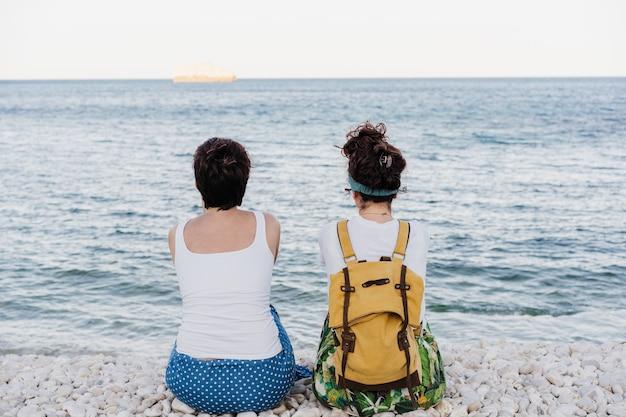 Vista posteriore di una coppia lesbica rilassata seduta in spiaggia durante il tramonto. l'amore è amore e concetto lgtbi