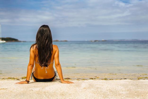Punto di vista posteriore di rilassamento della donna abbronzata nella riva della spiaggia