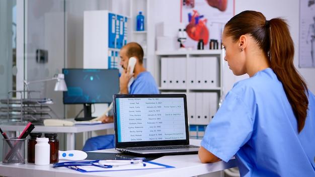 Vista posteriore del medico residente che controlla gli appuntamenti sul laptop mentre il collega risponde al telefono offrendo consulenza medica al paziente remoto, assistente che lavora nella clinica ospedaliera