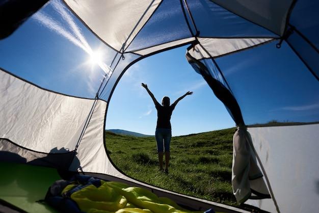 Vista posteriore sulla viandante esile della ragazza che solleva le mani nell'aria, godendo della mattina soleggiata nelle montagne.