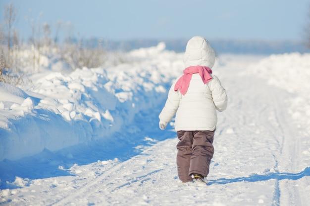 La vista posteriore della piccola femmina indossa abiti invernali caldi, passeggiate durante il freddo inverno, piace giocare all'aperto