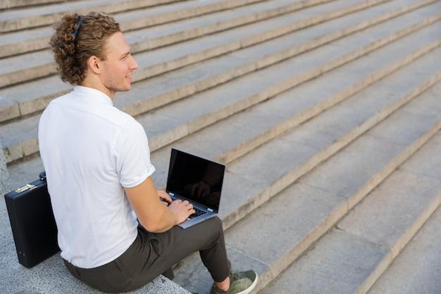 Vista posteriore di un uomo d'affari riccio sorridente con valigetta e computer portatile seduto vicino alle scale mentre guarda lontano