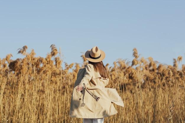 Vista posteriore della ragazza alla moda in cappotto beige e cappello sullo sfondo di canne secche e cielo blu