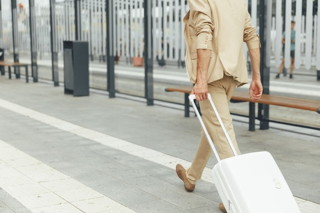 Vista posteriore di imprenditore di successo in abito beige che cammina alla fermata dell'autobus con la valigia bianca in mano