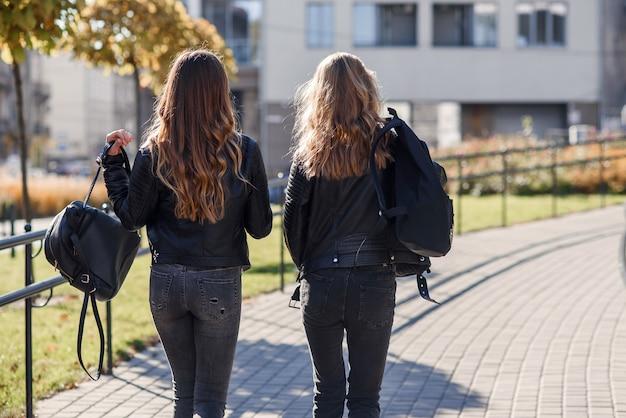 Vista posteriore di amiche graziose adolescenti con zaini che camminano per strada.
