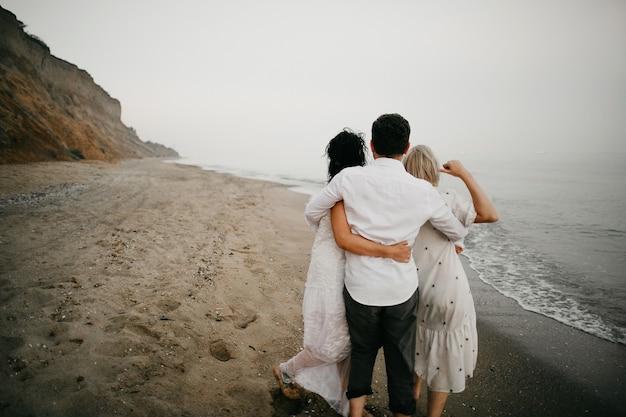 Vista posteriore di tre persone adulte che si abbracciano insieme sulla spiaggia e guardano l'oceano