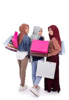 Vista posteriore di tre donne hijab che trasportano sacco di carta dopo lo shopping insieme