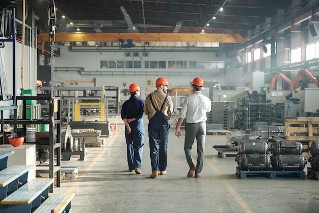 Vista posteriore di tre giovani operai contemporanei di impianto industriale che camminano lungo la grande fabbrica e comunicano