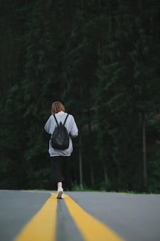Vista posteriore sulla ragazza turistica che cammina vicino alla foresta di conifere