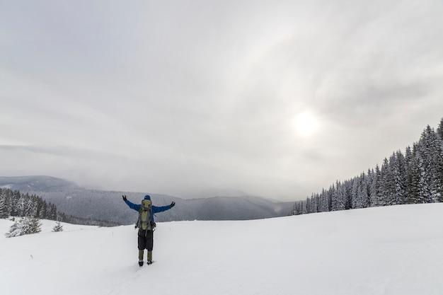 Vista posteriore del turista escursionista in abiti caldi