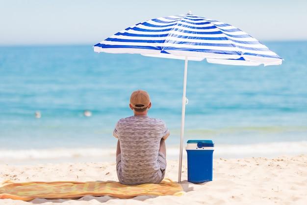 Vista posteriore del turista seduto sulla spiaggia sotto l'ombrellone vicino al dispositivo di raffreddamento con bevande fredde