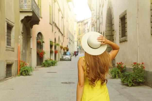 Vista posteriore della donna turistica a piedi e tenendo il cappello in via pignolo street nel centro storico di bergamo, italia.