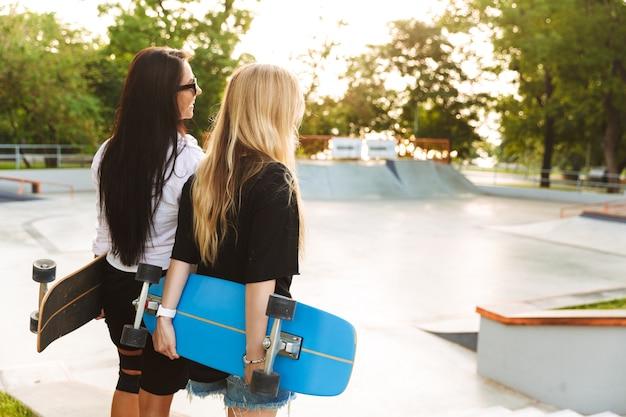 Vista posteriore di due giovani adolescenti attraenti che tengono longboard mentre si trovano allo skatepark
