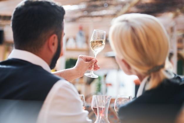 Vista posteriore di due cavisti professionisti contemporanei che studiano le caratteristiche del campione di vino in flauto