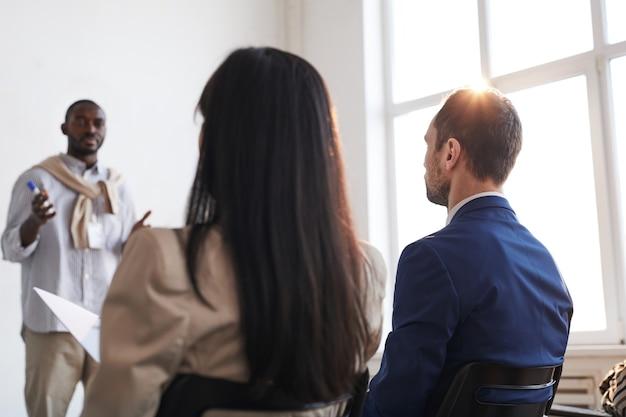 Vista posteriore di due persone che ascoltano il coach aziendale mentre sono seduti su sedie tra il pubblico durante una conferenza o un seminario, copia spazio