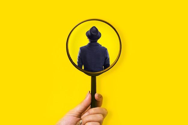 Vista posteriore di un uomo non identificato in lente d'ingrandimento, concetto di ricerca di persona, risorse umane e miglior impiegato