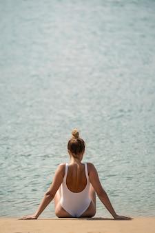 Vista posteriore di una donna sconosciuta a prendere il sole sulla spiaggia contro il mare. indossa costumi da bagno bianchi. è da sola.