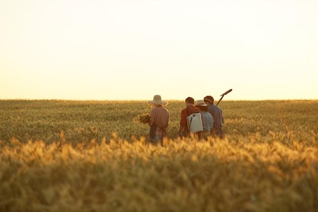 Ampio angolo di vista posteriore ai lavoratori che tengono gli strumenti mentre si cammina attraverso il campo dorato nella luce del tramonto, copia dello spazio