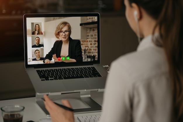 Punto di vista posteriore di una donna a casa che parla con il suo capo e altri colleghi in una videochiamata su un computer portatile. la donna di affari parla con i colleghe su una conferenza della webcam.