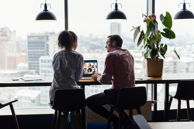 Vista posteriore di donna e uomo in ufficio con una videochiamata