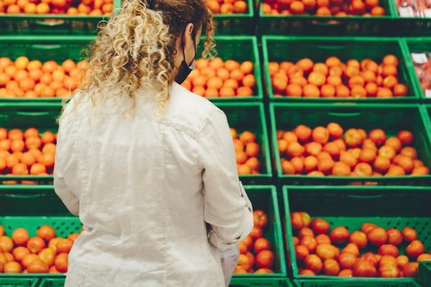 Punto di vista posteriore della donna al mercato che compra frutta o pomodori. persone in attività di acquisto di cibo in un grande negozio. donna che indossa la maschera vista posteriore
