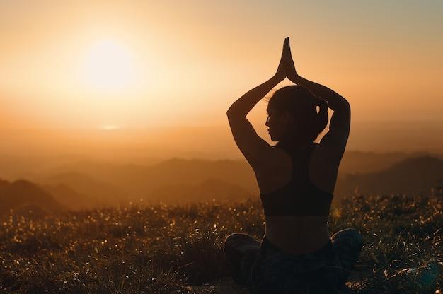 Una vista posteriore della silhouette di una donna che pratica lo yoga in natura. posizione del loto con le mani sopra la testa