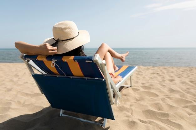 Punto di vista posteriore della donna che si siede sulla sedia di spiaggia che esamina il mare