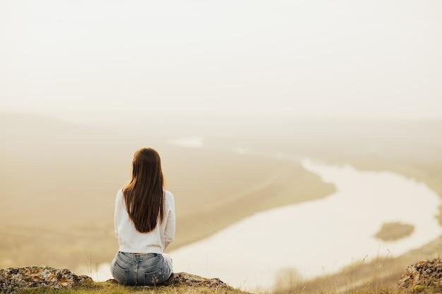 Vista posteriore della donna seduta in cima alla collina e guardando il fiume nel tramonto di sera.